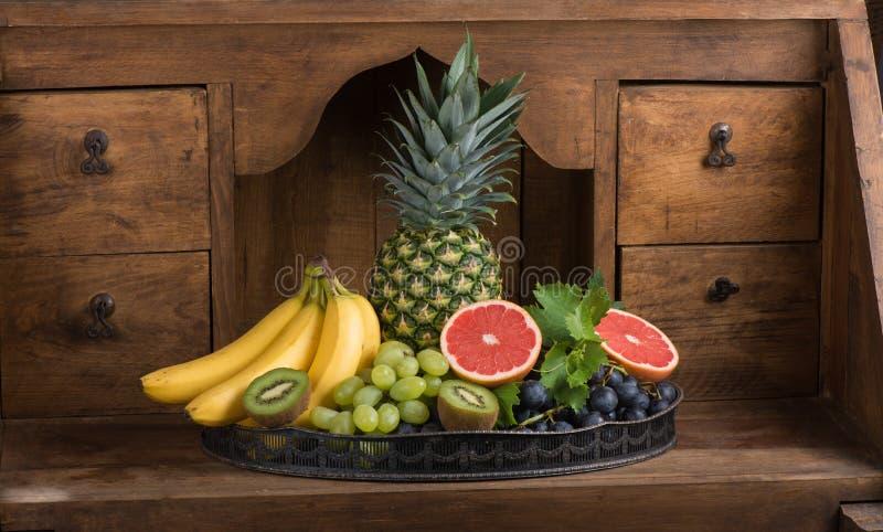 Frutos (abacaxi, banana, uvas, quivi, toranja) em um prato fotografia de stock