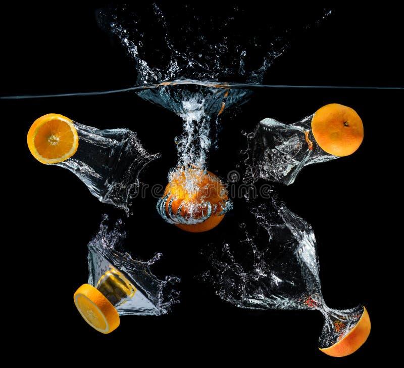 Frutos alaranjados droping da fatia da água imagem de stock
