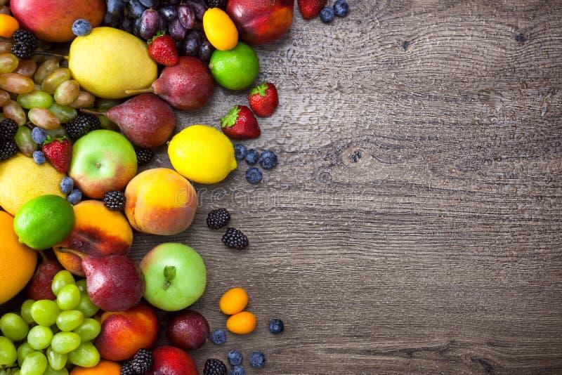 Frutos coloridos na tabela de madeira com gotas da água e espaço da cópia imagens de stock