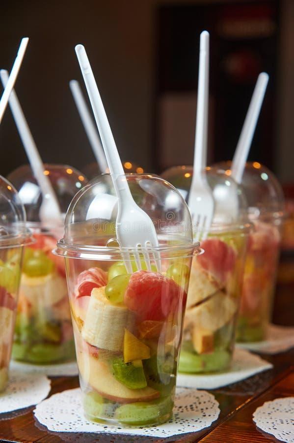 Frutos cortados no copo plástico restauração saudável do alimento Salada de fruta Barra da aptidão dos cereais para a dieta imagens de stock