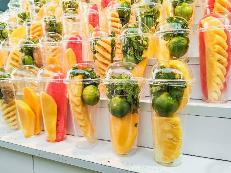 Frutos da mistura em um vidro pl?stico em prateleiras de madeira fotos de stock royalty free