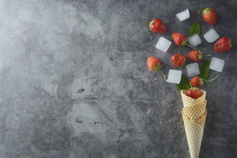 Frutos da morango no cone do waffle, sobre o fundo escuro, vista superior Espa?o t?mido imagem de stock royalty free
