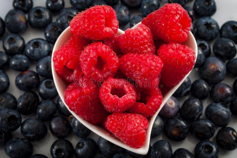 Frutos de baga frescos e conceito saudável comer com mirtilos e as framboesas misturados em uma bacia dada forma coração fotografia de stock