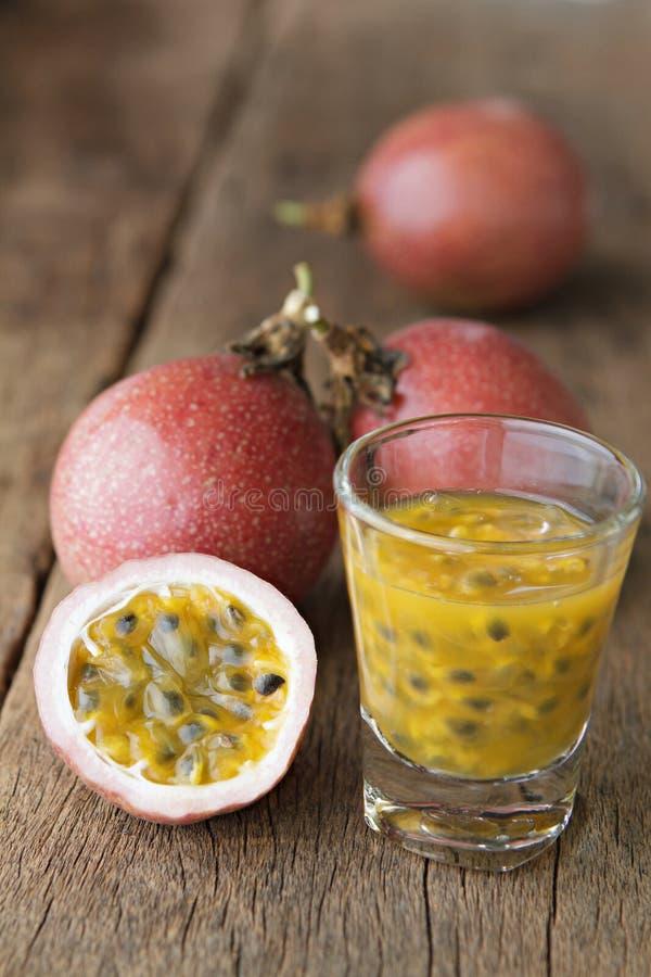 Frutos de paixão com vidro de sucos de fruto da paixão em de madeira fotos de stock