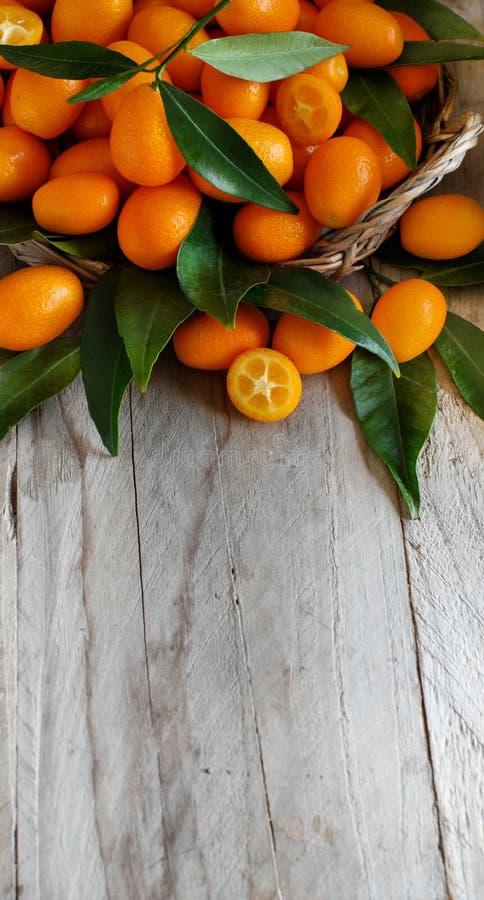Frutos do Kumquat em um fundo de madeira cinzento fotos de stock