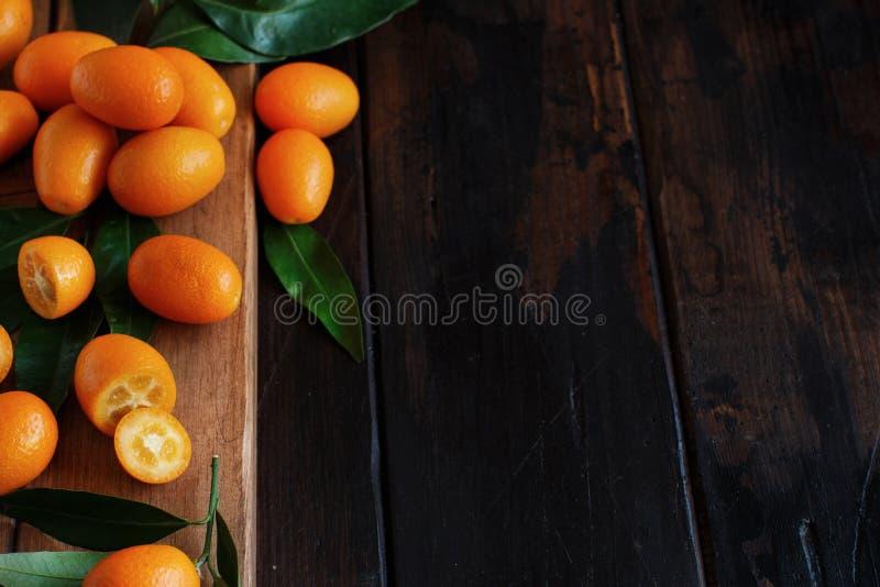 Frutos do Kumquat em um fundo de madeira escuro foto de stock