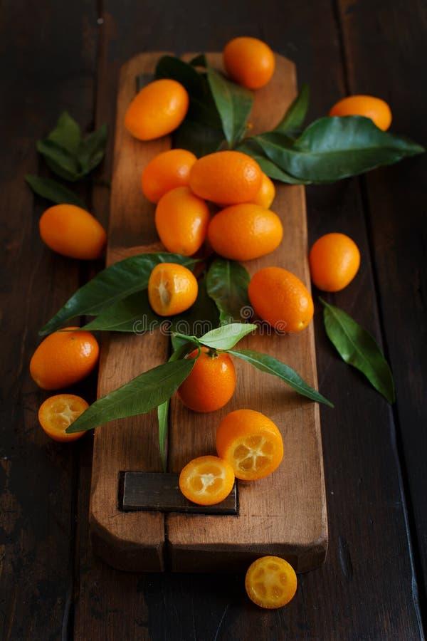Frutos do Kumquat em um fundo de madeira escuro foto de stock royalty free