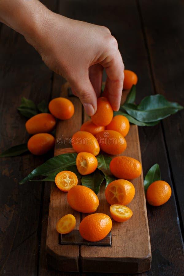 Frutos do Kumquat em um fundo de madeira escuro imagens de stock royalty free