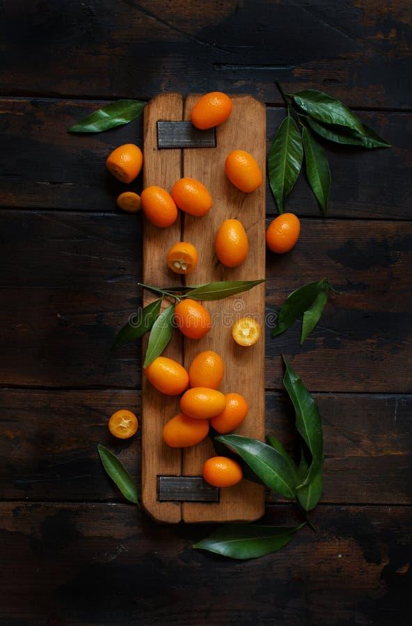 Frutos do Kumquat em um fundo de madeira escuro imagens de stock