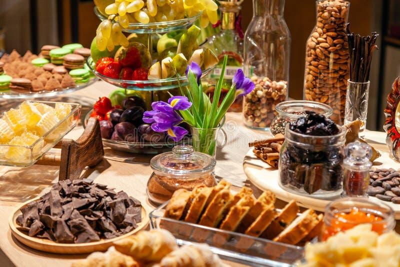 Frutos dos petiscos do close up, os frescos e secada, partes queijo parmesão, favos de mel, chocolate escuro, varas de canela, po imagem de stock royalty free