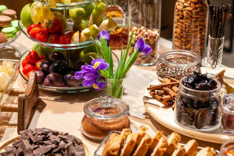 Frutos dos petiscos do close up, os frescos e secada, partes queijo parmesão, favos de mel, chocolate escuro, varas de canela, po imagens de stock