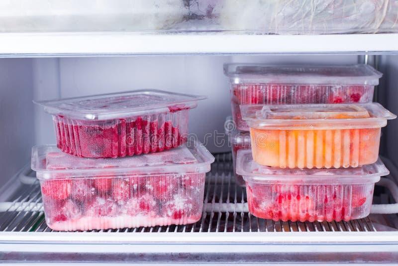 Frutos e bagas congelados em um recipiente no congelador imagens de stock