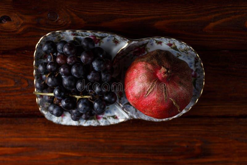 Frutos em uma placa, em uvas e em rom? imagem de stock