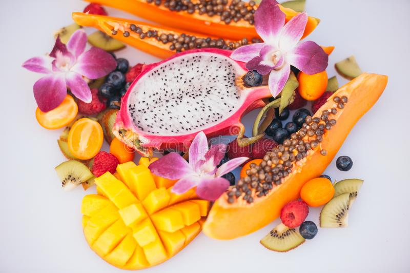 Frutos exóticos orgânicos frescos no fundo branco Fruto maduro do dargon, papaia, quivi, manga com o kumquat, decorado com boni imagem de stock