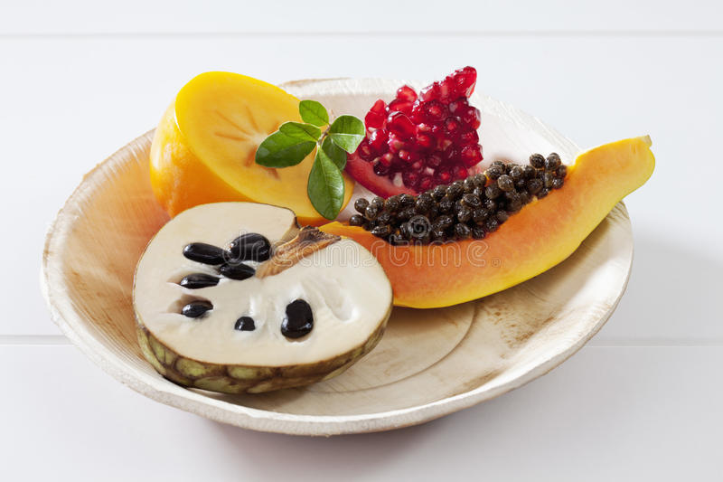 Frutos exóticos, papaia, romã, cherimólia, fatias do caqui na placa no fundo branco fotos de stock