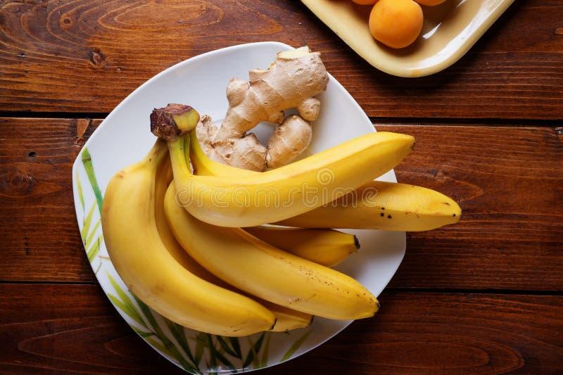Frutos frescos banana e abricós que colocam na tabela de madeira Configura??o lisa fotos de stock