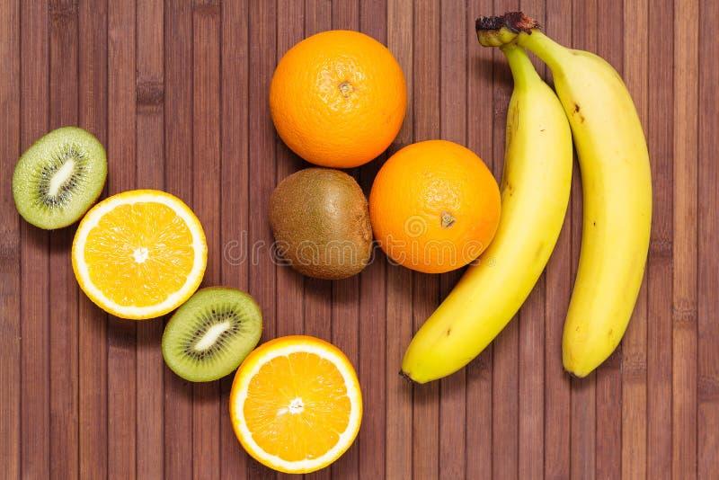 Frutos frescos banana, quivi, laranja isolada no fundo de madeira Alimento saudável Uma mistura de fruta fresca Grupo de citrinas fotos de stock royalty free