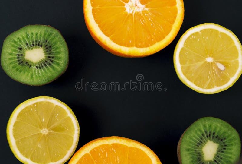 Frutos frescos coloridos em um fundo escuro Laranja, o mandarino, quivi, limão Fundo da fruta Conceito do alimento do verão foto de stock