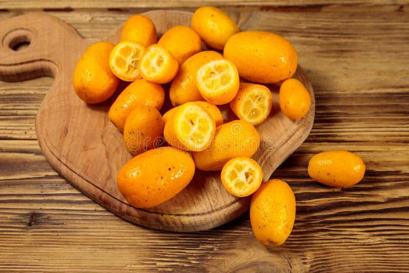 Frutos frescos do kumquat na tabela de madeira imagens de stock royalty free