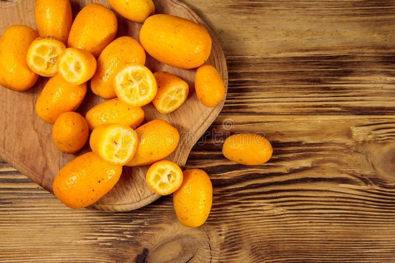 Frutos frescos do kumquat na tabela de madeira fotografia de stock
