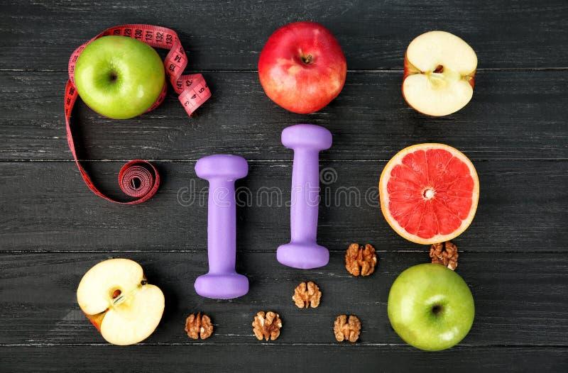 Frutos frescos e pesos no fundo de madeira Fa?a dieta o alimento foto de stock
