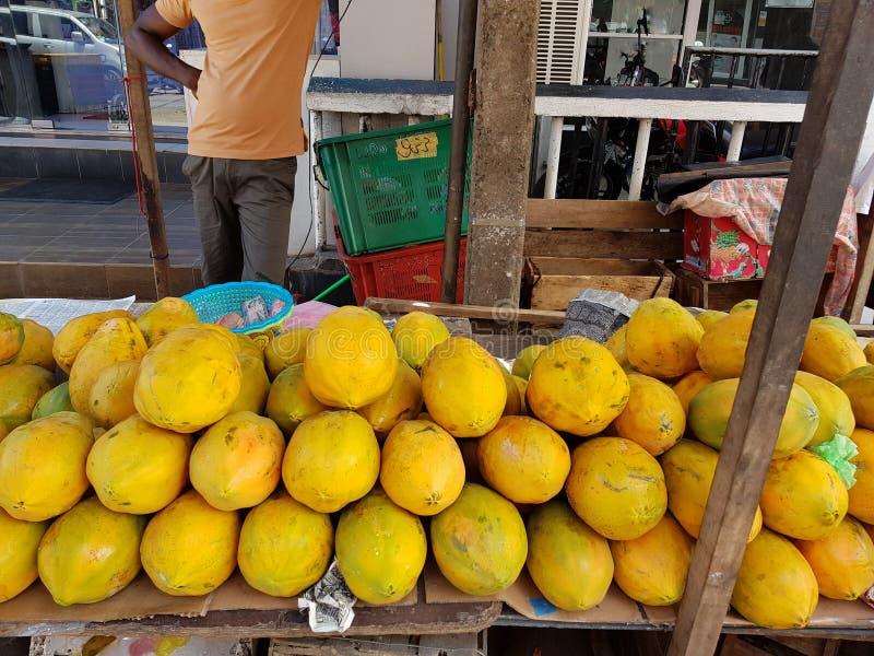 Frutos maduros da papaia amarela empilhados em um mercado local das frutas e legumes imagens de stock royalty free