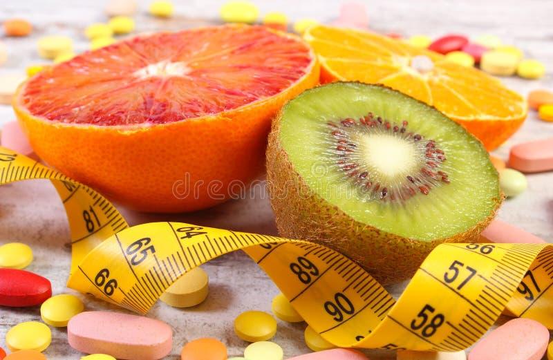 Frutos naturais, centímetro e comprimidos médicos, emagrecimento, escolha entre a nutrição saudável e suplementos médicos fotos de stock