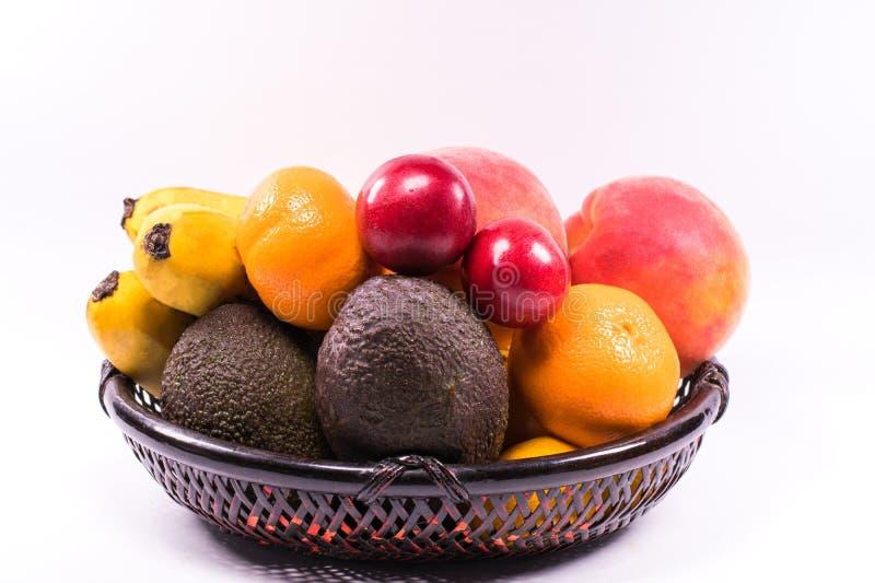 Frutos orgânicos frescos na cesta de vime no fundo branco com c imagens de stock