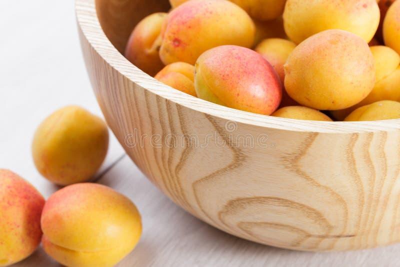 frutos orgânicos maduros dos abricós na bacia de madeira da árvore de cinza em um fundo de madeira branco fotografia de stock