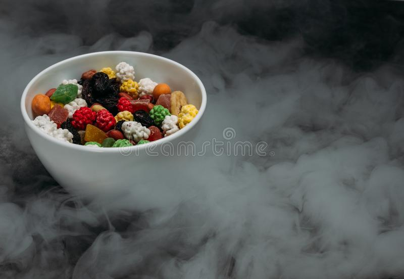 Frutos secados em uma bacia na tabela no fumo imagem de stock royalty free