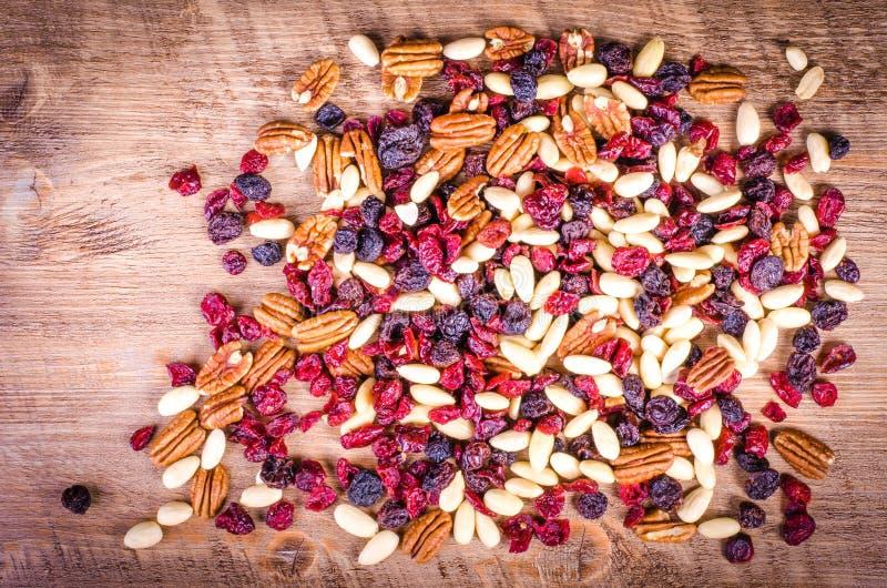 Frutos secados - noz-pecã, arando, passa, amêndoa em de madeira imagem de stock royalty free