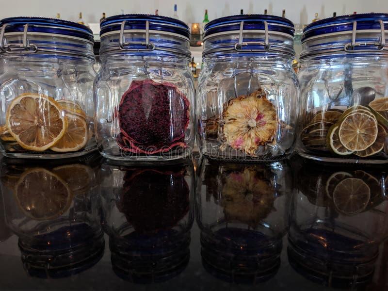 Frutos secos en un tarro de cristal fruta, naranjas y piña del dragón imagen de archivo libre de regalías