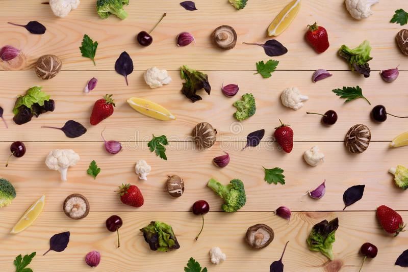 Fruts, vegetables and berries over wooden background. Variety of colorful food ingredients, healthy diet concept. Top view. stock photo