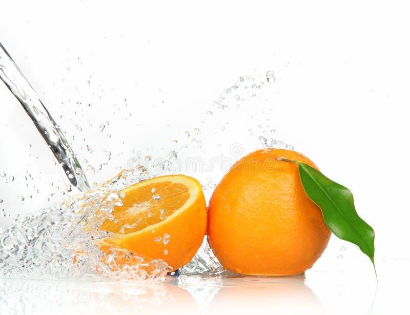 Frutta arancione con la spruzzatura dell'acqua immagine stock