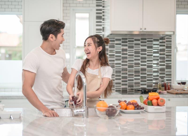 Frutta asiatica di lavaggio della donna nel lavandino e nell'uomo bello che stanno accanto lei immagini stock libere da diritti