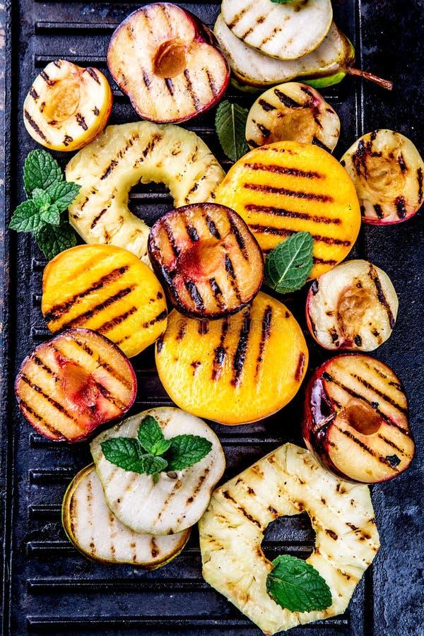 Frutta cotta La griglia fruttifica - ananas, pesche, prugne, avocado, pera sul bordo nero della griglia del ghisa fotografia stock libera da diritti