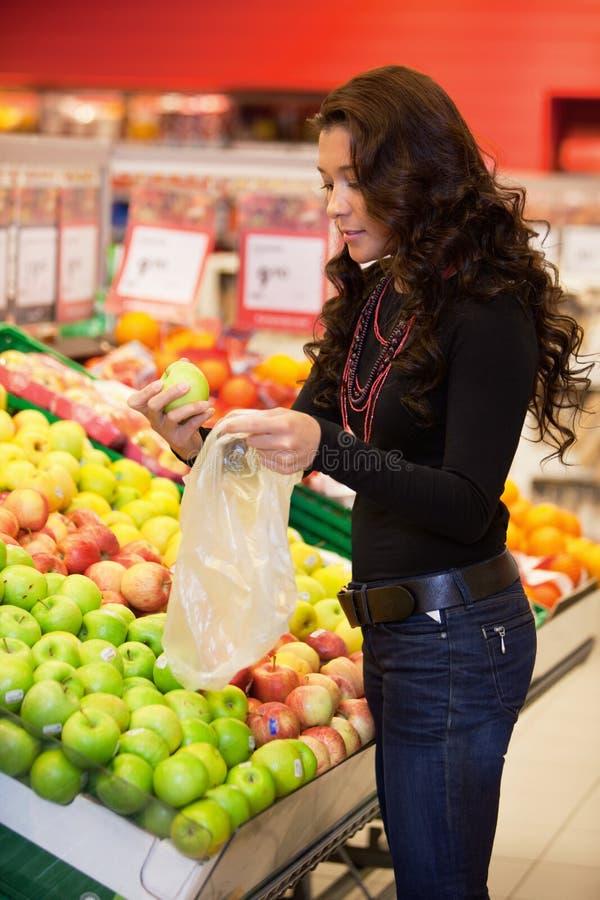 Frutta d'acquisto della giovane donna fotografie stock libere da diritti