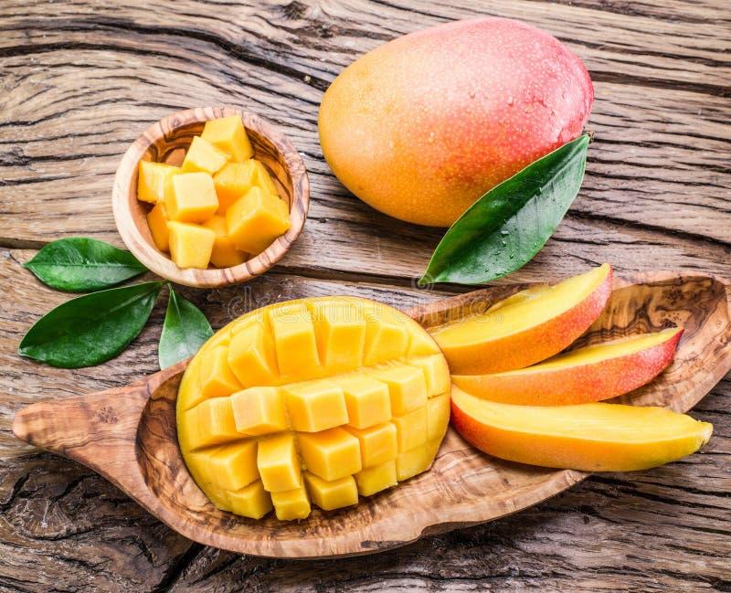Frutta del mango e cubi del mango su una tavola di legno fotografia stock libera da diritti