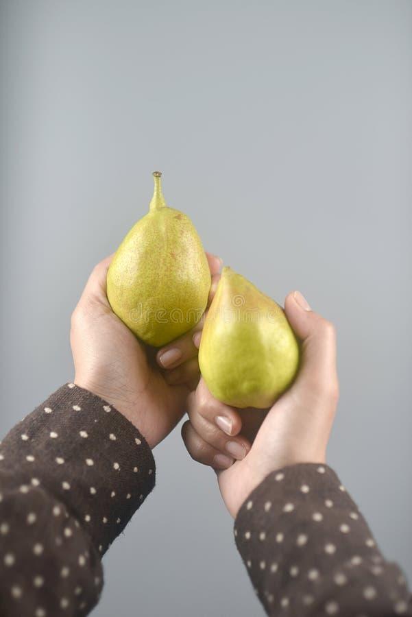 Frutta della pera sulle mani delle donne con il cappotto marrone su fondo grigio chiaro Immagine verticale fotografia stock libera da diritti
