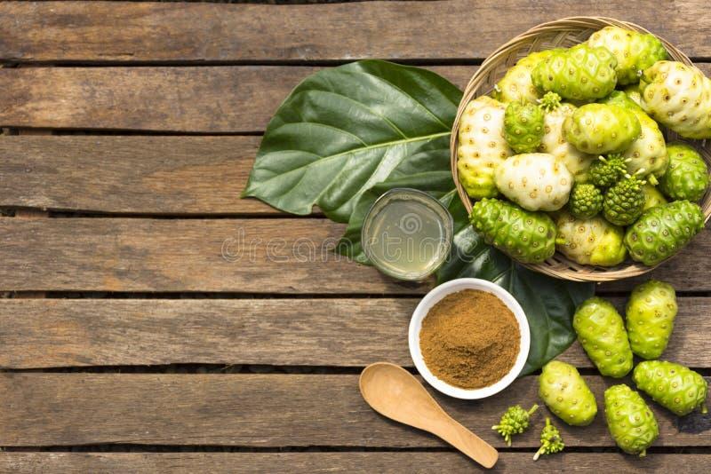 Frutta di Noni e noni nel canestro con il succo di noni e polvere di noni sulla tavola di legno Vista superiore fotografia stock libera da diritti
