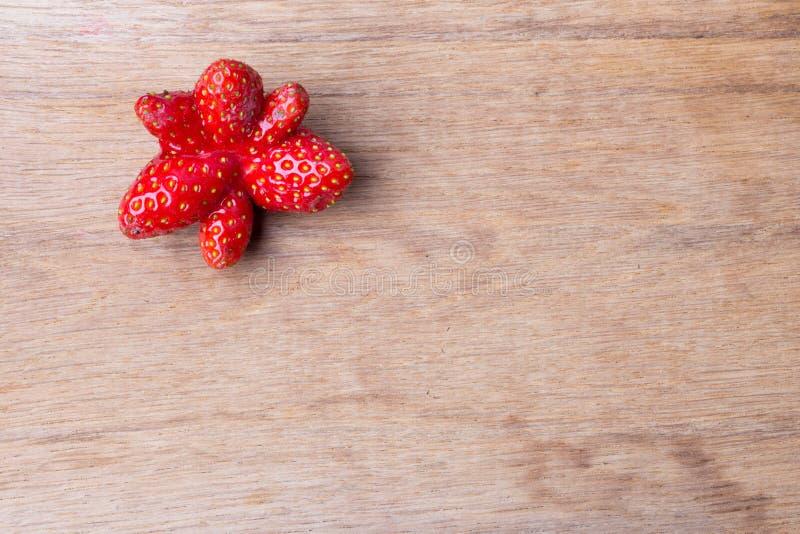 Frutta dispari rossa della fragola sulla tavola di legno immagini stock