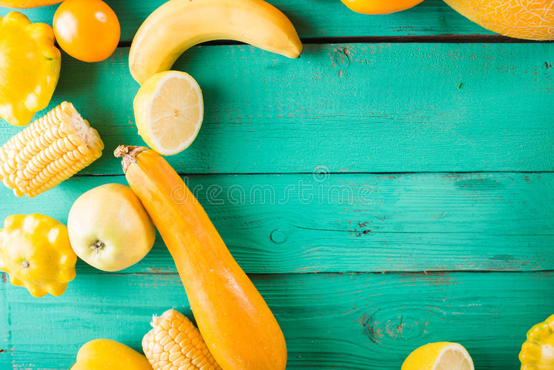 Frutta e verdure gialle su un fondo di legno del turchese Natura morta festiva variopinta immagine stock libera da diritti
