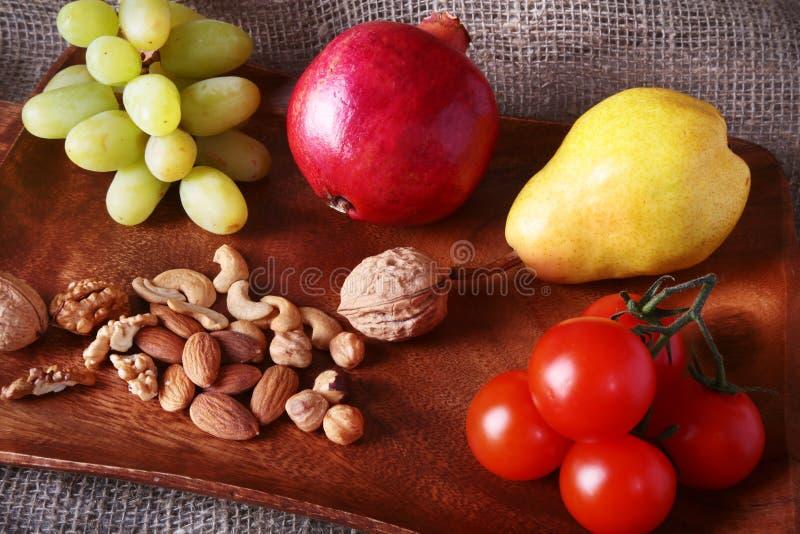 Frutta e verdure organiche fresche sul vassoio di legno del servizio Mela assortita, pera, uva, pomodori e dadi immagine stock libera da diritti