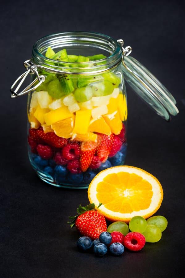 Frutta fresca davanti al barattolo di vetro in pieno dei frutti variopinti fotografia stock