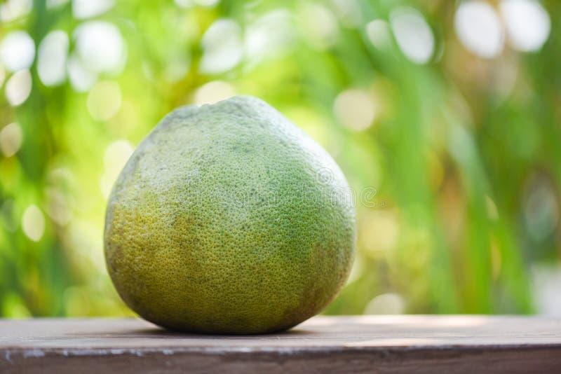 Frutta fresca del pomelo sul fondo di legno della natura di verde della tavola immagine stock