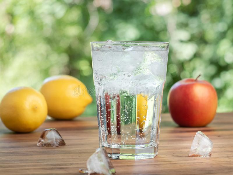 Frutta fresca e vetro con acqua ed i cubetti di ghiaccio di fusione, fine su Limoni gialli, mela rossa, cubetti di ghiaccio e vet immagine stock