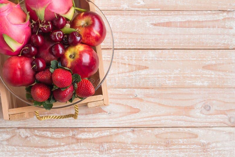 Frutta fresca mista in ciotola e scatola su fondo di legno fotografia stock