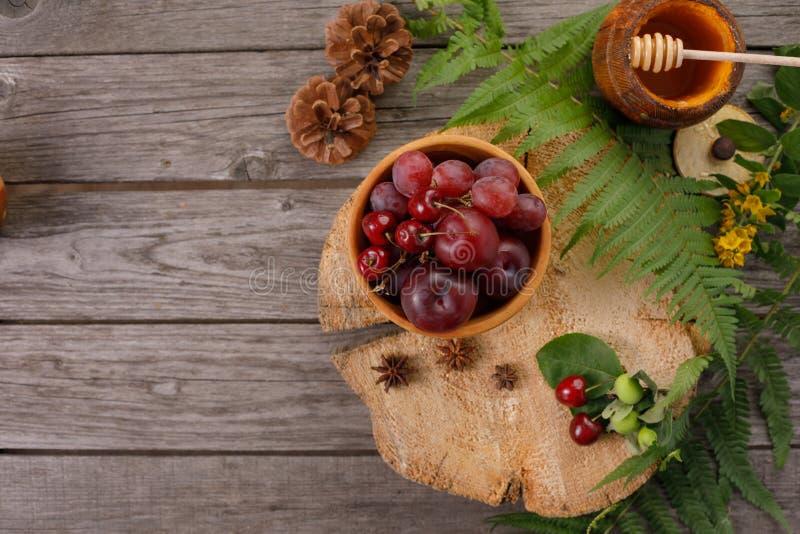 Frutta matura del raccolto Fondo con le foglie della felce, le prugne rosse e l'uva Annata su legno invecchiato con lo spazio del fotografia stock