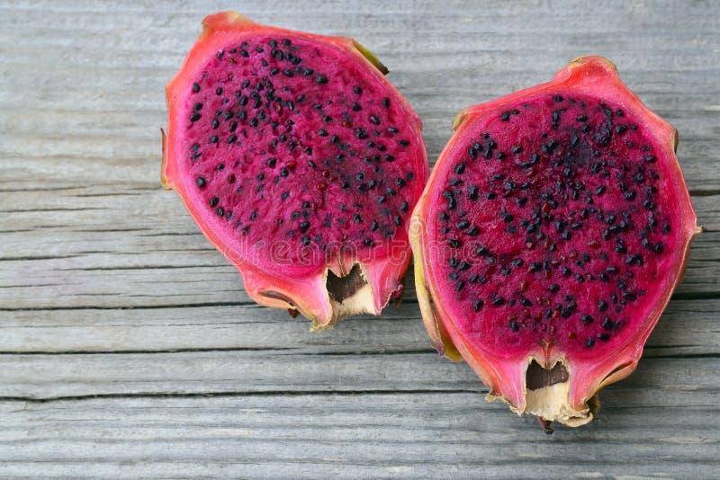 Frutta rosa matura esotica del drago o di Pitaya La frutta tropicale rossa di Pitahaya ha tagliato a metà sulla vecchia tavola di fotografie stock