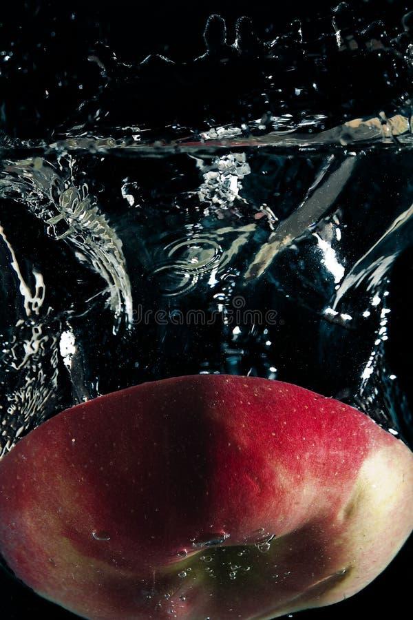 Frutta rossa che galleggia in acqua fotografia stock libera da diritti